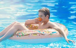 Happy cute little boy teenager lying on inflatable donut ring with orange in swimming pool. Active games on water, vacation. Holidays concept. Chocolate donut royalty free stock photos