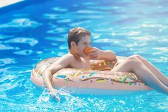Happy cute little boy teenager lying on inflatable donut ring with orange in swimming pool. Active games on water, vacation. Holidays concept. Chocolate donut royalty free stock images