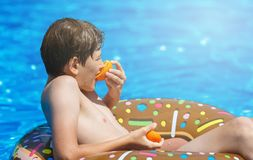 Happy cute little boy teenager lying on inflatable donut ring with orange in swimming pool. Active games on water, vacation. Holidays concept. Chocolate donut stock image
