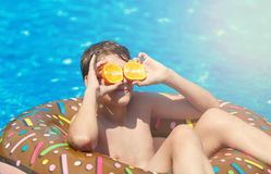 Happy cute little boy teenager lying on inflatable donut ring with orange in swimming pool. Active games on water, vacation. Holidays concept. Chocolate donut stock photography