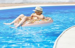 Happy cute little boy teenager lying on inflatable donut ring with orange in swimming pool. Active games on water, vacation. Holidays concept. Chocolate donut stock photo