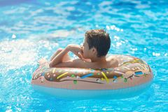 Happy cute little boy teenager lying on an inflatable donut ring in swimming pool. Active games on water, vacation, holidays. Concept. Chocolate donut. Cool fun stock images