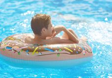 Happy cute little boy teenager lying on an inflatable donut ring in swimming pool. Active games on water, vacation, holidays. Concept. Chocolate donut. Cool fun stock image