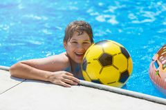 Happy cute little boy teenager in swimming pool. Active games on water, vacation, holidays concept. Chocolate donut. royalty free stock photo