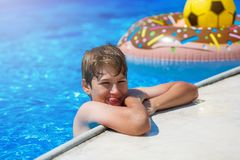 Happy cute little boy teenager in swimming pool. Active games on water, vacation, holidays concept. Chocolate donut. stock photo