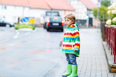 Happy cute little boy walking in city through rain Stock Photography