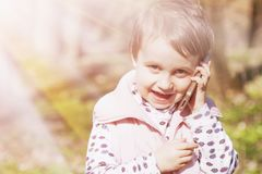 Happy cute little child girl talking phone outdoors Happy child royalty free stock photography