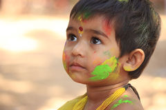 Happy cute little child on holi color festival. stock image