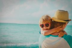 Happy cute little daughter hug dad at beach. Vacation stock photography
