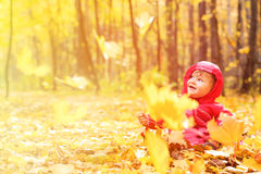 Happy cute little girl in autumn leaves Royalty Free Stock Image