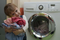 Happy cute little girl with clothes doing laundry in home interior. Happy cute little girl doing laundry in home interior. Mother's helper. 2 year old stock image