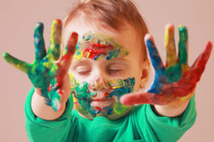 Happy cute little girl with colorful painted hands Royalty Free Stock Photography