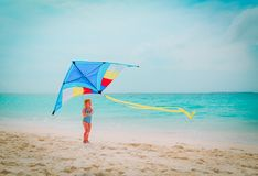 Happy cute little girl flying a kite on beach. Happy cute little girl flying a kite on tropical beach Royalty Free Stock Images