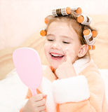 Happy cute little girl in hair curlers with mirror Stock Photo