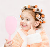 Happy cute little girl in hair curlers with mirror applying cream Stock Image