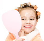 Happy cute little girl in hair curlers with mirror applying cream Stock Images