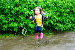 Happy cute little girl jumping in puddle after rain in summer. Happy cute little girl jumping in puddle after rain Royalty Free Stock Photos
