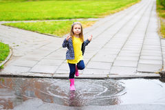 Happy cute little girl jumping in puddle after rain in summer Royalty Free Stock Photography