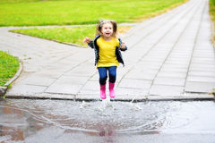 Happy cute little girl jumping in puddle after rain in summer stock photography