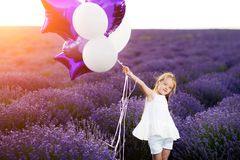 Happy cute little girl in lavender field with purple balloons. Freedom concept. Royalty Free Stock Photos