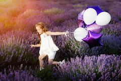 Happy cute little girl in lavender field with purple balloons. Freedom concept. Stock Photos