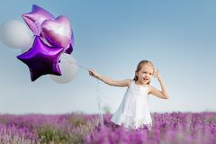 Happy cute little girl in lavender field with purple balloons. Freedom concept. Royalty Free Stock Photo