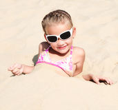 Happy cute little girl lying in sand Royalty Free Stock Photos