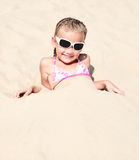 Happy cute little girl lying in sand Royalty Free Stock Images