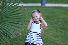 Happy cute little girl in palm summer hot day in the holidays Stock Photo