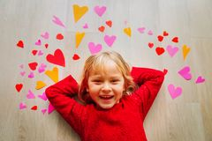 Happy cute little girl play with hearts from paper, valentine day. Celebration royalty free stock image