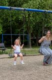 Happy little girl at playground swinging Royalty Free Stock Photos