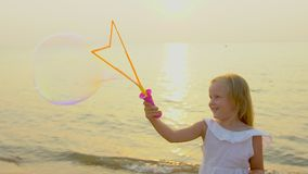 Happy cute Little Girl Playing wit Soap Bubbles outdoor on the beach during beautiful sunset happy vacation time in slow