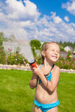 Happy cute little girl pouring water from a hose Royalty Free Stock Images
