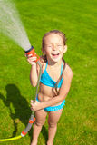Happy cute little girl pouring water from a hose Royalty Free Stock Photo