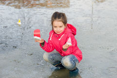 Happy cute little girl in rain boots playing with handmade colorful ships in the spring creek standing in water Stock Images