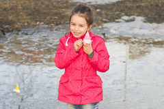Happy cute little girl in rain boots playing with handmade ships in the spring creek standing in water Stock Image