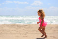 Happy cute little girl run on sand beach Stock Image