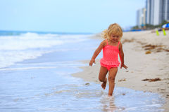 Happy cute little girl run on sand beach Stock Photos