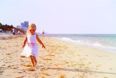Happy cute little girl running on beach Stock Photo