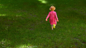Happy cute little girl running in the park. Happiness. Royalty Free Stock Images