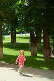 Happy cute little girl running in the park. Happiness. Royalty Free Stock Photos