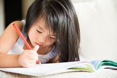 Happy cute little girl smiling and holding red pencil stock image