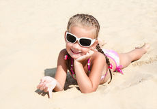 Happy cute little girl in sunglasses lying on the sand Royalty Free Stock Photography