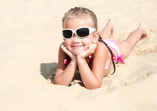 Happy cute little girl in sunglasses lying on the sand Stock Photography