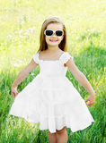 Happy cute little girl in sunglasses on the meadow Stock Images