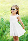 Happy cute little girl in sunglasses on the meadow Royalty Free Stock Photos