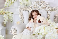 Happy cute little girl with a toys in a light studio.  on white background. Happy brunett little girl with a big toy bear in a studio.  on white background royalty free stock photo