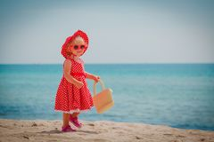 Happy cute little girl walk on sand beach. Vacation concept royalty free stock photo