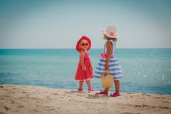 Happy cute little girls with beach bags at sea. Vacation stock images