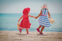 Happy cute little girls with beach bags at sea. Vacation royalty free stock photo
